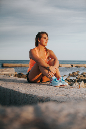 women sitting: Blonde woman in fitness clothes, sitting in the nature.