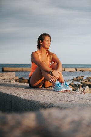 mujeres sentadas: Mujer rubia en ropa de fitness, sentado en la naturaleza.