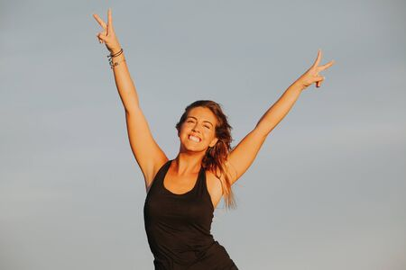 Blonde fitness woman raising arms and doing victory sign with the hands. Success concept.