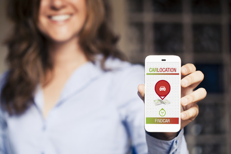 Locating car app in a mobile phone. Woman holding it in the hand. Standard-Bild