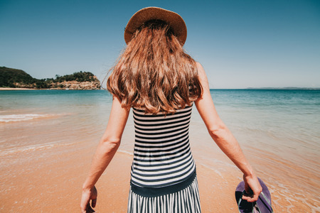 Woman in her back entering into a beautiful Australian beach. Stock Photo