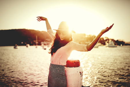 woman sunset: Happy woman posing in front of the ocean with arms up. Beautiful filtered sunset light.