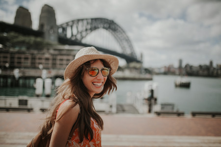 Happy smiling woman exploring Sydney, with Harbour Bridge in the background. 写真素材