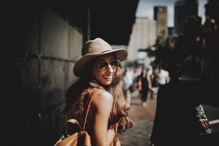 Smiling happy woman walking in a Sydney street and turning around to look at the camera. Stock Photo