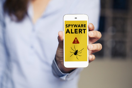 Spyware alert in a mobile phone held by hand.