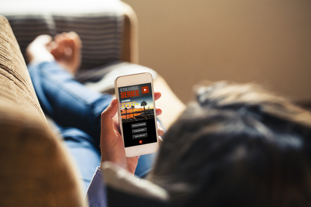 Woman watching tv series in a mobile phone app, while rest at home.