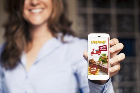 휴대 전화 화면에서 음식 휴대 전화 앱을 가져갑니다. 스톡 콘텐츠