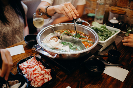 dipping: Korean hot pot meal. Hands taking food with chopsticks. Stock Photo