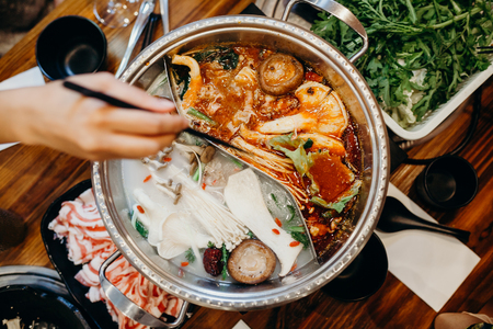 Korean hot pot meal. Hands taking food with chopsticks. Archivio Fotografico