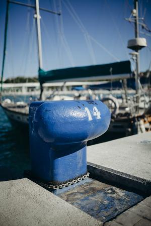 bollard: Blue aged boat mooring at port Stock Photo