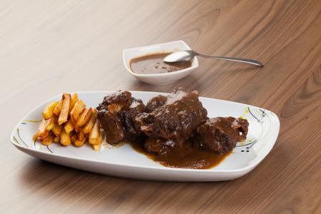 白いテーブルにフライド ポテトと牛テール料理