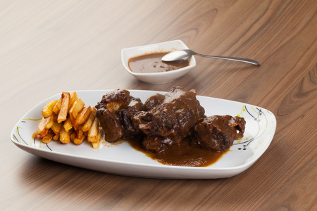 Bull tail dish with fried potatoes on white table Standard-Bild