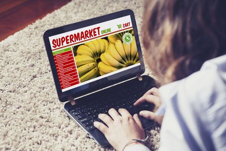 woman laptop: Woman doing her supermarket shopping by internet with a laptop while rest at home Stock Photo