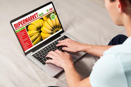 L'homme fait son épicerie par internet avec un ordinateur portable à la maison Banque d'images - 83767626