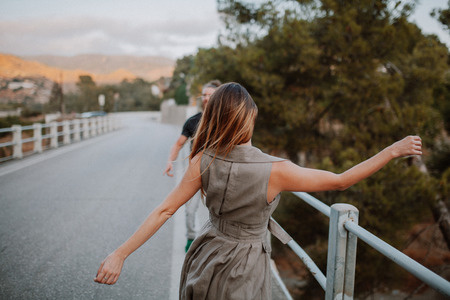 Woman dancing approaching to her boyfriend on a road