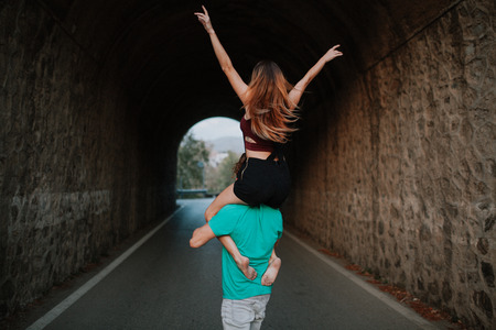 cute guy: Young rad couple walking on their backs into a tunnel across the road