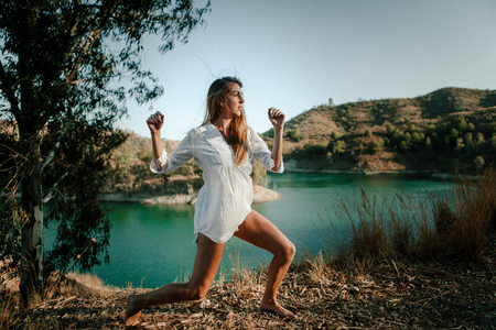 Woman performing contemporary dance outdoors, with a river in the background Stock Photo
