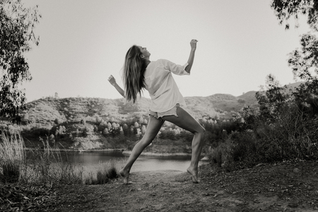 Woman in white shirt dancing in nature with a lake in the background. Black and white
