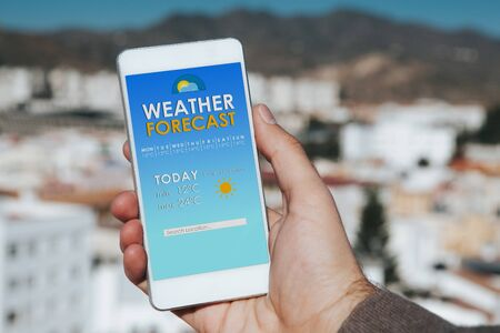 Hand holding a cellphone with weather information in the screen.