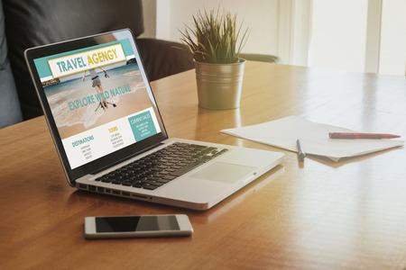 Ordenador portátil con un sitio web de agencia de viajes en la pantalla de la oficina.