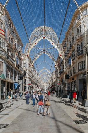 MALAGA, SPAIN - DECEMBER 5th, 2017: View of Malaga Larios Street life, with Christmas ornament, and people walking along it, on December 5th, 2017.