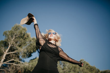 Young blonde woman jumping in nature with black sunglasses and clothes and a hat.