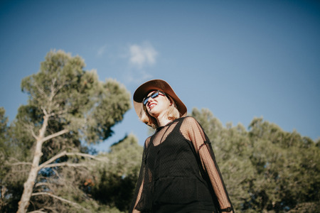 Low angle portrait of cute smiling blonde woman exploring in nature with sunglasses and black clothes.