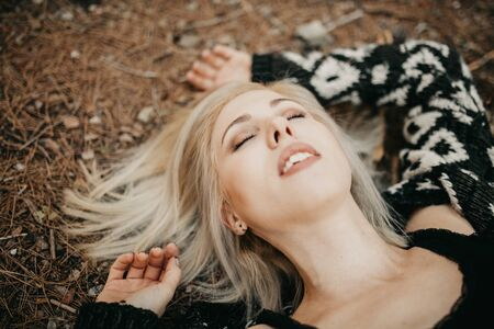 calm blonde girl lying down in the forest portrait.