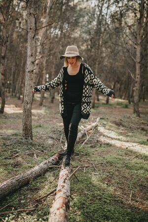 Woman with a hat walking over a fallen tree trunk in the forest.