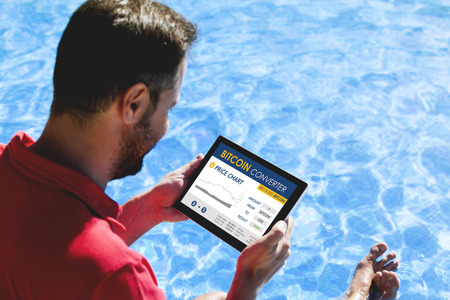 Man trading bitcoin price in a bitcoin converter website with a tablet, while sitting outdoors.
