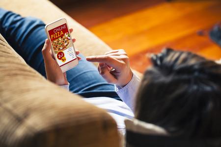 App de compras de pizza em uma tela do telefone móvel. Mulher segurando o telefone inteligente na mão.