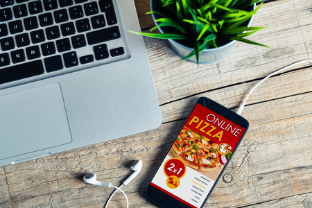 Mobile phone with Pizza shop app in the screen over a wooden table at the office. Stock Photo