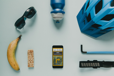 Cycling accessories on blue background, and GPS route on mobile phone screen.