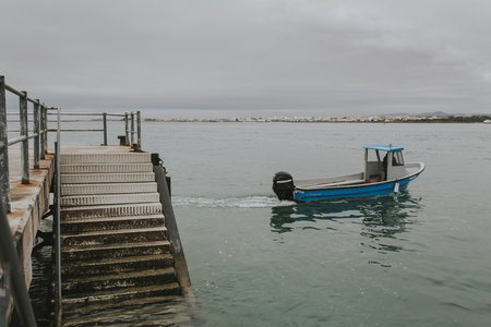 Armona Island, Portugal - March 23, 2018: Little blue boat navigating from Armona Island pier to Olhao, in Portugal. Foto de archivo - 111317947