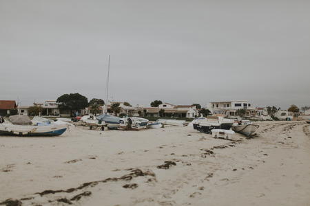 Armona Island, Portugal - March 23, 2018: Little boats docked in the Armona island beach in a cloudy day, at Olhao, Portugal. Editorial
