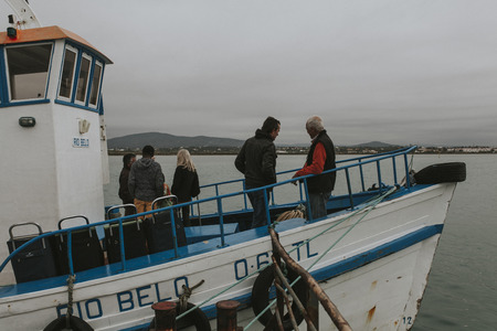 Armona Island, Portugal - March 23, 2018: Olhao ferry boat at Armona Island pier ready to go in a cloudy day, in Olhao, Portugal. Foto de archivo - 111317960