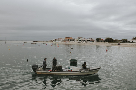 Armona Island, Portugal - March 23, 2018: Three men arriving to Armona Island pier in a little boat in a cloudy day in Olhao, Portugal. Editorial