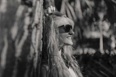 Black and white portrait of young blonde woman in the forest, smiling and with sunglasses on.