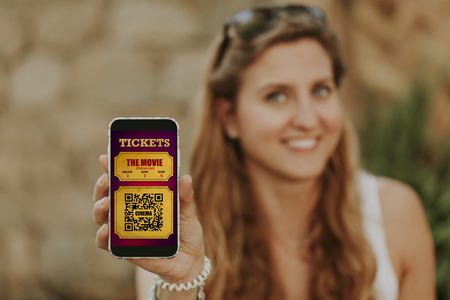 Cute blonde woman holding a mobile phone in the hand with cinema tickets in the screen. Stock Photo