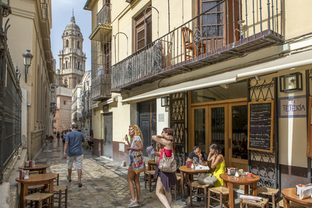 MALAGA, SPAIN - September 2nd, 2018: Tourists having a tea in a coffee shop with the Cathedral in the background, during a journey in the city center of Malaga, Spain. 스톡 콘텐츠 - 111375180