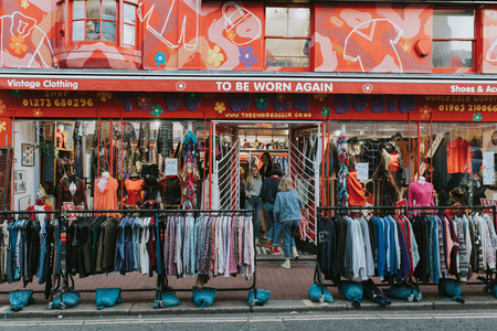 BRIGHTON, ENGLAND - October 24th, 2018: Vintage clothing shop facade with a lot of clothes in the street, and people entering inside it. Editorial