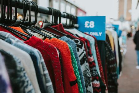 Portant d'une boutique vintage avec des maillots et des manteaux, prêts à acheter, au milieu de la rue.