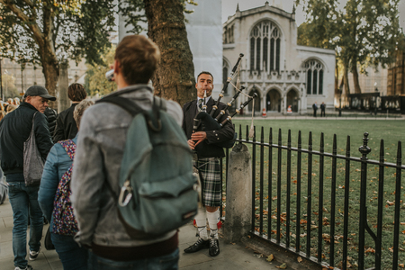 LONDON, ENGLAND - October 25th, 2018: Bagpiper playing pipe at Westminster Abbey entrance, while tourist walk around by the sidewalk.