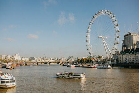 LONDON, ENGLAND - 25th October, 2018: River Thames viewed from Westminster Bridge, with touristic ferrys navigating, and London Eye in the background, in London, United Kingdom