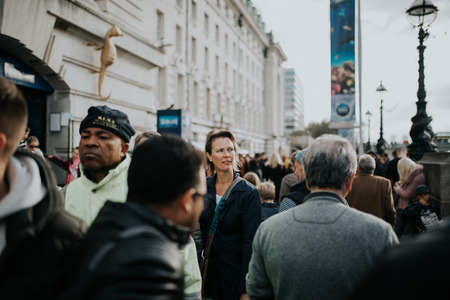 LONDON, ENGLAND - 25th October, 2018: Woman walking inside the crowd across The Queens Walk, in a sunny day in London, Uk.