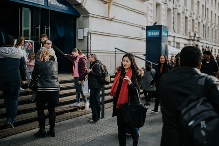 LONDON, ENGLAND - 25th October, 2018: Asian woman walking inside the crowd across The Queens Walk, in a sunny day in London, Uk.