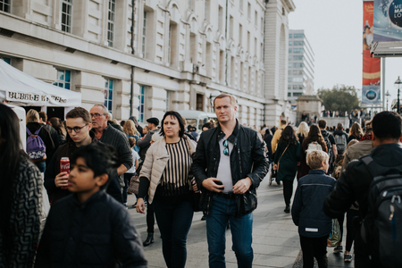 LONDON, ENGLAND - 25th October, 2018: Couple walking inside the crowd across The Queens Walk, in a sunny day in London, Uk. Editorial