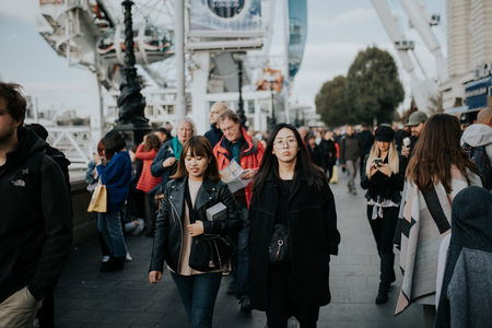 LONDON, ENGLAND - 25th October, 2018: Two young asian women walking inside the crowd across The Queens Walk, in a sunny day in London, Uk.