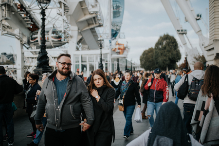 LONDON, ENGLAND - 25th October, 2018: Young couple walking inside the crowd across The Queens Walk, in a sunny day in London, Uk.