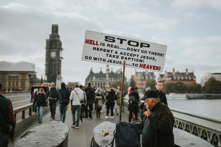 LONDON, ENGLAND - 25th October, 2018: A eccentric man showing a message in a board related to Jesus, in the middle of Wetminster Bridge, with tourists around him, in London, United Kingdom.